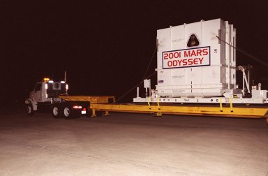 The 2001 Mars Odyssey spacecraft leaves the KSC Shuttle Landing Facility on the bed of a transport trailer. The spacecraft is being moved to the Spacecraft Assembly and Encapsulation Facility 2 (SAEF-2) located in the KSC Industrial Area. The spacecraft arrived at the SLF aboard an Air Force C-17 cargo airplane that brought it from Denver, Colo.., location of the Lockheed Martin plant where the spacecraft was built. In the SAEF, Odyssey will undergo final assembly and checkout. This includes installation of two of the three science instruments, integration of the three-panel solar array, and a spacecraft functional test. It will be fueled and then mated to an upper stage booster, the final activities before going to the launch pad. Launch is planned for April 7, 2001 the first day of a 21-day planetary window. Mars Odyssey will be inserted into an interplanetary trajectory by a Boeing Delta II launch vehicle from Pad A at Complex 17 at the Cape Canaveral Air Force Station, Fla. The spacecraft will arrive at Mars on Oct. 20, 2001, for insertion into an initial elliptical capture orbit. Its final operational altitude will be a 250-mile-high, Sun-synchronous polar orbit. Mars Odyssey will spend two years mapping the planet's surface and measuring its environment