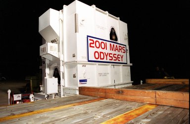 The 2001 Mars Odyssey spacecraft sits on the bed of the trailer that will take it from KSC?s Shuttle Landing Facility to the Spacecraft Assembly and Encapsulation Facility 2 (SAEF-2) located in the KSC Industrial Area. The spacecraft arrived at the SLF aboard an Air Force C-17 cargo airplane that brought it from Denver, Colo.., location of the Lockheed Martin plant where the spacecraft was built. In the SAEF Odyssey will undergo final assembly and checkout. This includes installation of two of the three science instruments, integration of the three-panel solar array, and a spacecraft functional test. It will be fueled and then mated to an upper stage booster, the final activities before going to the launch pad. Launch is planned for April 7, 2001 the first day of a 21-day planetary window. Mars Odyssey will be inserted into an interplanetary trajectory by a Boeing Delta II launch vehicle from Pad A at Complex 17 at the Cape Canaveral Air Force Station, Fla. The spacecraft will arrive at Mars on Oct. 20, 2001, for insertion into an initial elliptical capture orbit. Its final operational altitude will be a 250-mile-high, Sun-synchronous polar orbit. Mars Odyssey will spend two years mapping the planet's surface and measuring its environment