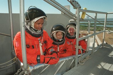 STS-98 Mission Specialists Robert Curbeam, Marsha Ivins and Thomas Jones try out the three-person slidewire basket, part of the equipment used for emergency egress from the launch pad. The basket slides along a 1200-foot wire to the landing zone below and nearby bunker. The crew has been taking part in Terminal Countdown Demonstration Test activities, which include the simulated countdown and emergency egress training at the pad. STS-98 is the seventh construction flight to the International Space Station, carrying as payload the U.S. Lab Destiny, a key element in the construction of the ISS. Launch of STS-98 is scheduled for Jan. 19 at 2:11 a.m. EST