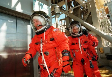 Fully dressed in their launch and entry suits, STS-98 Mission Specialists Thomas Jones (left), Marsha Ivins and Robert Curbeam practice a speedy exit from the Fixed Service Structure during emergency egress training. They are heading for the slidewire baskets that slide along a 1200-foot wire to the landing zone below and nearby bunker. The crew has been taking part in Terminal Countdown Demonstration Test activities, which include the simulated countdown and emergency egress training at the pad. STS-98 is the seventh construction flight to the International Space Station, carrying as payload the U.S. Lab Destiny, a key element in the construction of the ISS. Launch of STS-98 is scheduled for Jan. 19 at 2:11 a.m. EST
