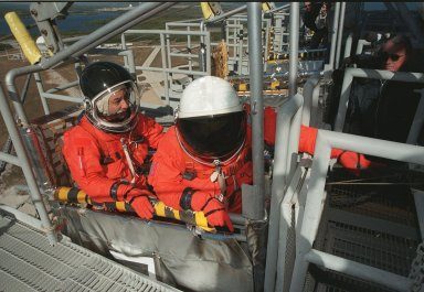 During emergency egress training at the 195-foot level of the Fixed Service Structure, Pilot Mark Polansky settles in the slidewire basket while Commander Ken Cockrell reaches for the release handle. The basket slides along a 1200-foot wire to the landing zone below and nearby bunker. The crew has been taking part in Terminal Countdown Demonstration Test activities, which include the simulated countdown and emergency egress training at the pad. STS-98 is the seventh construction flight to the International Space Station, carrying as payload the U.S. Lab Destiny, a key element in the construction of the ISS. Launch of STS-98 is scheduled for Jan. 19 at 2:11 a.m. EST