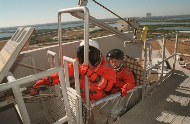 During emergency egress training at the 195-foot level of the Fixed Service Structure, Mission Specialist Marsha Ivins take her place in the slidewire basket while Mission Specialist Robert Curbeam reaches for the release handle. The basket slides along a 1200-foot wire to the landing zone below and nearby bunker. The crew has been taking part in Terminal Countdown Demonstration Test activities, which include the simulated countdown and emergency egress training at the pad. STS-98 is the seventh construction flight to the International Space Station, carrying as payload the U.S. Lab Destiny, a key element in the construction of the ISS. Launch of STS-98 is scheduled for Jan. 19 at 2:11 a.m. EST