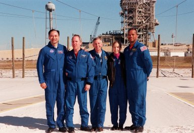 KENNEDY SPACE CENTER, FLA -- After a media briefing at Launch Pad 39A, the STS-98 crew poses in the slidewire basket landing zone. Standing, left to right, are Pilot Mark Polansky, Mission Specialist Thomas Jones, Commander Ken Cockrell and Mission Specialists Marsha Ivins and Robert Curbeam. All are at KSC to take part in Terminal Countdown Demonstration Test activities, which include emergency egress training and a simulated launch countdown. STS-98 is the seventh construction flight to the International Space Station, carrying as payload the U.S. Lab Destiny, a key element in the construction of the ISS. Launch of STS-98 is scheduled for Jan. 19 at 2:11 a.m