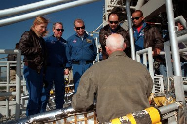 The STS-98 crew listens to instructions on use of the slidewire basket, part of emergency egress equipment from the launch pad. At the 195-foot level of the Fixed Service Structure are Mission Specialists Marsha Ivins and Thomas Jones, Commander Ken Cockrell, Pilot Mark Polansky and Mission Specialist Robert Curbeam. The crew is at KSC to take part in Terminal Countdown Demonstration Test activities, which include emergency egress training and a simulated launch countdown at the pad. STS-98 is the seventh construction flight to the International Space Station, carrying as payload the U.S. Lab Destiny, a key element in the construction of the ISS. Launch of STS-98 is scheduled for Jan. 19 at 2:11 a.m
