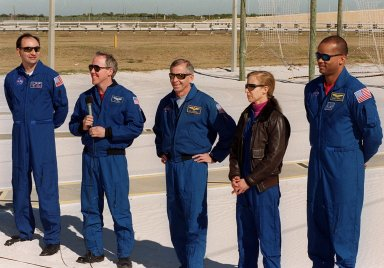 KENNEDY SPACE CENTER, FLA. -- A humorous question from the media (out of view) produces smiles among the STS-98 crew during a briefing at Launch Pad 39A. Standing, left to right, are Pilot Mark Polansky, Mission Specialist Thomas Jones (with microphone), Commander Ken Cockrell, and Mission Specialists Marsha Ivins and Robert Curbeam. All are at KSC to take part in Terminal Countdown Demonstration Test activities, which include emergency egress training and a simulated launch countdown. STS-98 is the seventh construction flight to the International Space Station, carrying as payload the U.S. Lab Destiny, a key element in the construction of the ISS. Launch of STS-98 is scheduled for Jan. 19 at 2:11 a.m