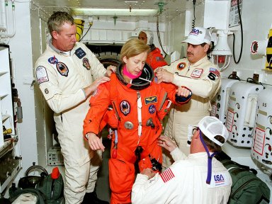 In the White Room, members of the closeout crew help STS-98 Mission Specialist Marsha Ivins (center) with her launch and entry suit before she enters Atlantis for a simulated launch countdown. The White Room is an environmental chamber at the end of the orbiter access arm that mates with the orbiter to allow personnel to enter the orbiter?s crew compartment. The STS-98 crew is taking part in Terminal Countdown Demonstration Test activities, which also include emergency egress training at the pad. STS-98 is the seventh construction flight to the International Space Station, carrying as payload the U.S. Lab Destiny, a key element in the construction of the ISS. Launch of STS-98 is scheduled for Jan. 19 at 2:11 a.m. EST