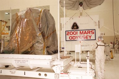 Workers in the Spacecraft Assembly and Encapsulation Facility 2 move the shipping crate away from the 2001 Mars Odyssey spacecraft, at left on the stand. Odyssey is still covered by a protective sheet. The spacecraft, which arrived from Denver, Colo., Jan. 4, will undergo final assembly and checkout in the SAEF-2. That includes installation of two of the three science instruments, integration of the three-panel solar array, and a spacecraft functional test. Launch aboard a Boeing Delta II launch vehicle from Pad A, Complex 17, CCAFS, is planned for April 7, 2001 the first day of a 21-day planetary window. The spacecraft will arrive at Mars on Oct. 20, 2001, for insertion into an initial elliptical capture orbit. Its final operational altitude will be a 250-mile-high, Sun-synchronous polar orbit. Mars Odyssey will spend two years mapping the planet?s surface and measuring its environment