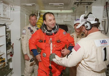 In the White Room, STS-98 Pilot Mark Polansky gets help with his launch and entry suit before entering Atlantis for a simulated launch countdown. The White Room is an environmental chamber at the end of the orbiter access arm that mates with the orbiter to allow personnel to enter the orbiter?s crew compartment. The STS-98 crew is taking part in Terminal Countdown Demonstration Test activities, which also include emergency egress training at the pad. STS-98 is the seventh construction flight to the International Space Station, carrying as payload the U.S. Lab Destiny, a key element in the construction of the ISS. Launch of STS-98 is scheduled for Jan. 19 at 2:11 a.m. EST