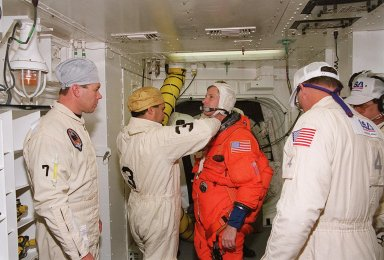 In the White Room at Launch Pad 39A, STS-98 Commander Ken Cockrell (center) gets help from the closeout crew with his launch and entry suit before entering Atlantis for a simulated launch countdown. The White Room is an environmental chamber at the end of the orbiter access arm that mates with the orbiter to allow personnel to enter the orbiter?s crew compartment. The STS-98 crew is taking part in Terminal Countdown Demonstration Test activities, which also include emergency egress training at the pad. STS-98 is the seventh construction flight to the International Space Station, carrying as payload the U.S. Lab Destiny, a key element in the construction of the ISS. Launch of STS-98 is scheduled for Jan. 19 at 2:11 a.m. EST