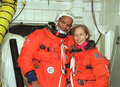 In the White Room, STS-98 Mission Specialists Robert Curbeam and Marsha Ivins pose for a photo before entering Atlantis for a simulated launch countdown. The White Room is an environmental chamber at the end of the orbiter access arm that mates with the orbiter to allow personnel to enter the orbiter?s crew compartment. The STS-98 crew is taking part in Terminal Countdown Demonstration Test activities, which also include emergency egress training at the pad. STS-98 is the seventh construction flight to the International Space Station, carrying as payload the U.S. Lab Destiny, a key element in the construction of the ISS. Launch of STS-98 is scheduled for Jan. 19 at 2:11 a.m. EST