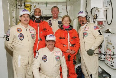The closeout crew in the White Room pose with two of the STS-98 crew. Kneeling in front is United Space Alliance Mechanical Technician George Schramm. Standing, left to right, are USA Mechanical Technician Vinny Difranzo, Mission Specialist Robert Curbeam, NASA Quality Assurance Specialist Ken Strite, Mission Specialist Marsha Ivins, and USA Orbiter Vehicle Closeout Chief Travis Thompson. The White Room is an environmental chamber at the end of the orbiter access arm that mates with the orbiter to allow personnel to enter the orbiter?s crew compartment. The STS-98 crew is getting ready to enter Atlantis for a simulated launch countdown, part of Terminal Countdown Demonstration Test activities. STS-98 is the seventh construction flight to the International Space Station, carrying as payload the U.S. Lab Destiny, a key element in the construction of the ISS. Launch of STS-98 is scheduled for Jan. 19 at 2:11 a.m. EST