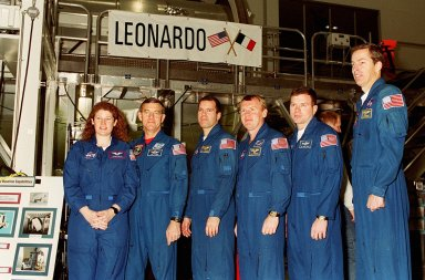 KENNEDY SPACE CENTER, FLA. -- The crew of STS-102, plus Expedition Two astronauts, poses in front of Leonardo, the Multi-Purpose Logistics Module that will fly on the mission. From left are Susan Helms and James Voss, part of Expedition Two; Mission Specialists Paul W. Richards and Andrew S.W. Thomas; Pilot James M. Kelly; and Commander James D. Wetherbee. Not shown is cosmonaut Yuri Usachev, who is also part of Expedition Two. The MPLM is the first of three such pressurized modules that will serve as the International Space Station?s ?moving vans,? carrying laboratory racks filled with equipment, experiments and supplies to and from the Space Station aboard the Space Shuttle. Leonardo will be launched March 1, 2001, on Shuttle mission STS-102. On that flight, Leonardo will be filled with equipment and supplies to outfit the U.S. laboratory module Destiny. The mission will also be carrying the Expedition Two crew to the Space Station, replacing the Expedition One crew who will return on Shuttle Discovery