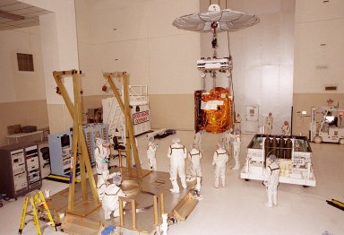 In the Spacecraft Assembly & Encapsulation Facility -2, workers help guide the 2001 Mars Odyssey Orbiter [ http://mars.jpl.nasa.gov/2001/ ] to a workstand (left). The spacecraft carries three science instruments: the Thermal Emission Imaging System (THEMIS), the Gamma Ray Spectrometer (GRS), and the Mars Radiation Environment Experiment (MARIE). THEMIS will map the mineralogy and morphology of the Martian surface using a high-resolution camera and a thermal infrared imaging spectrometer. The GRS will achieve global mapping of the elemental composition of the surface and determine the abundance of hydrogen in the shallow subsurface. [The GRS is a rebuild of the instrument lost with the Mars Observer mission.] The MARIE will characterize aspects of the near-space radiation environment as related to the radiation-related risk to human explorers. The Mars Odyssey Orbiter is scheduled for launch on April 7, 2001, aboard a Delta 7925 rocket from Launch Pad 17-A, Cape Canaveral Air Force Station
