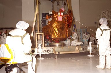 The 2001 Mars Odyssey Orbiter comes to rest on a workstand in the Spacecraft Assembly & Encapsulation Facility -2. Workers check the spacecraft?s position. The Mars Odyssey Orbiter carries three science instruments: the Thermal Emission Imaging System (THEMIS), the Gamma Ray Spectrometer (GRS), and the Mars Radiation Environment Experiment (MARIE). THEMIS will map the mineralogy and morphology of the Martian surface using a high-resolution camera and a thermal infrared imaging spectrometer. The GRS will achieve global mapping of the elemental composition of the surface and determine the abundance of hydrogen in the shallow subsurface. [The GRS is a rebuild of the instrument lost with the Mars Observer mission.] The MARIE will characterize aspects of the near-space radiation environment as related to the radiation-related risk to human explorers. The Mars Odyssey Orbiter is scheduled for launch on April 7, 2001, aboard a Delta 7925 rocket from Launch Pad 17-A, Cape Canaveral Air Force Station