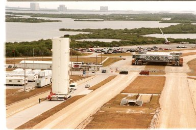 KENNEDY SPACE CENTER, FLA. -- An empty payload canister moves slowly to Launch Pad 39B alongside the crawlerway. In the near background is a crawler-transporter. Across the water, on the horizon can be seen buildings on the launch complexes at Cape Canaveral Air Force Station
