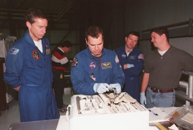 In the Orbiter Processing Facility bay 1, STS-102 crew members check out some of the equipment inside the tool caddy that is carried on launches. From left are Commander James D. Wetherbee, Mission Specialist Paul W. Richards and Pilot James W. Kelly. The crew is at KSC for Crew Equipment Interface Test activities. STS-102 is the 8th construction flight to the International Space Station and will carry the Multi-Purpose Logistics Module Leonardo. STS-102 is scheduled for launch March 1, 2001. On that flight, Leonardo will be filled with equipment and supplies to outfit the U.S. laboratory module Destiny. The mission will also be carrying the Expedition Two crew to the Space Station, replacing the Expedition One crew who will return on Shuttle Discovery