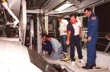 Members of the STS-102 crew and workers in the Orbiter Processing Facility bay 1 look over the windows of the orbiter Discovery, which will fly on their mission. Kneeling at left are Commander James D. Wetherbee and Pilot James W. Kelly; at right is Mission Specialist Paul W. Richards. The mission crew is at KSC for Crew Equipment Interface Test activities. STS-102 is the 8th construction flight to the International Space Station and will carry the Multi-Purpose Logistics Module Leonardo. STS-102 is scheduled for launch March 1, 2001. On that flight, Leonardo will be filled with equipment and supplies to outfit the U.S. laboratory module Destiny. The mission will also be carrying the Expedition Two crew to the Space Station, replacing the Expedition One crew who will return on Shuttle Discovery