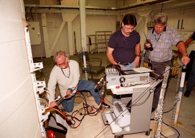 KENNEDY SPACE CENTER, FLA. -- Working near the top of a solid rocket booster, NASA and United Space Alliance SRB technicians hook up SRB cables to a CIRRUS computer for testing. From left are Jim Glass, with USA, performing a Flex test on the cable; Steve Swichkow, with NASA, and Jim Silviano, with USA, check the results on a computer. The SRB is part of Space Shuttle Atlantis, rolled back from Launch Pad 39A in order to conduct tests on the cables. A prior extensive evaluation of NASA?s SRB cable inventory on the shelf revealed conductor damage in four (of about 200) cables. Shuttle managers decided to prove the integrity of the system tunnel cables already on Atlantis before launching. Workers are conducting inspections, making continuity checks and conducting X-ray analysis on the cables. The launch has been rescheduled no earlier than Feb. 6.