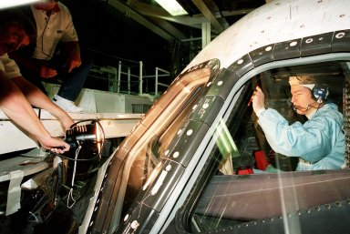 In the Orbiter Processing Facility bay 1, STS-102 Commander James D. Wetherbee checks out the window of Discovery from the inside while workers (left) check the outside.; The mission crew is at KSC for Crew Equipment Interface Test activities. STS-102 is the 8th construction flight to the International Space Station and will carry the Multi-Purpose Logistics Module Leonardo. STS-102 is scheduled for launch March 1, 2001. On that flight, Leonardo will be filled with equipment and supplies to outfit the U.S. laboratory module Destiny. The mission will also be carrying the Expedition Two crew to the Space Station, replacing the Expedition One crew who will return on Shuttle Discovery