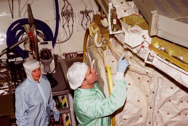 In the Orbiter Processing Facility bay 1, STS-102 Pilot James W. Kelly (right) points to a piece of equipment in Discovery?s payload bay. The crew is at KSC for Crew Equipment Interface Test activities. STS-102 is the 8th construction flight to the International Space Station and will carry the Multi-Purpose Logistics Module Leonardo. STS-102 is scheduled for launch March 1, 2001. On that flight, Leonardo will be filled with equipment and supplies to outfit the U.S. laboratory module Destiny. The mission will also be carrying the Expedition Two crew to the Space Station, replacing the Expedition One crew who will return on Shuttle Discovery