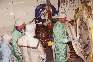 In the Orbiter Processing Facility bay 1, STS-102 Pilot James W. Kelly (left) looks on while Mission Specialist Paul W. Richards checks out equipment in Discovery?s payload bay. The crew is at KSC for Crew Equipment Interface Test activities. STS-102 is the 8th construction flight to the International Space Station and will carry the Multi-Purpose Logistics Module Leonardo. STS-102 is scheduled for launch March 1, 2001. On that flight, Leonardo will be filled with equipment and supplies to outfit the U.S. laboratory module Destiny. The mission will also be carrying the Expedition Two crew to the Space Station, replacing the Expedition One crew who will return on Shuttle Discovery