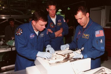 STS-102 Pilot James W. Kelly (left) and Mission Specialist Paul W. Richards look over equipment in the tool caddy that is carried on launches. Commander James D. Wetherbee (center) watches. The mission crew is at KSC for Crew Equipment Interface Test activities. STS-102 is the 8th construction flight to the International Space Station and will carry the Multi-Purpose Logistics Module Leonardo. STS-102 is scheduled for launch March 1, 2001. On that flight, Leonardo will be filled with equipment and supplies to outfit the U.S. laboratory module Destiny. The mission will also be carrying the Expedition Two crew to the Space Station, replacing the Expedition One crew who will return on Shuttle Discovery