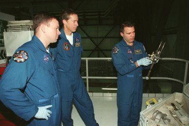 While STS-102 Pilot James W. Kelly and Commander James D. Wetherbee watch, Mission Specialist Paul W. Richards checks out a piece of equipment from the tool caddy below. The mission crew is at KSC for Crew Equipment Interface Test activities. STS-102 is the 8th construction flight to the International Space Station and will carry the Multi-Purpose Logistics Module Leonardo. STS-102 is scheduled for launch March 1, 2001. On that flight, Leonardo will be filled with equipment and supplies to outfit the U.S. laboratory module Destiny. The mission will also be carrying the Expedition Two crew to the Space Station, replacing the Expedition One crew who will return on Shuttle Discovery