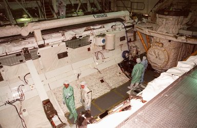 Members of the STS-102 crew check out Discovery?s payload bay in the Orbiter Processing Facility bay 1. Dressed in green, they are Mission Specialist Paul W. Richards (left) and Pilot James W. Kelly. The crew is at KSC for Crew Equipment Interface Test activities. Above their heads on the left side are two of the experiments being carried on the flight. STS-102 is the 8th construction flight to the International Space Station and will carry the Multi-Purpose Logistics Module Leonardo. STS-102 is scheduled for launch March 1, 2001. On that flight, Leonardo will be filled with equipment and supplies to outfit the U.S. laboratory module Destiny. The mission will also be carrying the Expedition Two crew to the Space Station, replacing the Expedition One crew who will return on Shuttle Discovery