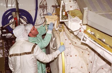 In the Orbiter Processing Facility bay 1, STS-102 Pilot James W. Kelly (right) checks out equipment in Discovery?s payload bay. The crew is at KSC for Crew Equipment Interface Test activities. STS-102 is the 8th construction flight to the International Space Station and will carry the Multi-Purpose Logistics Module Leonardo. STS-102 is scheduled for launch March 1, 2001. On that flight, Leonardo will be filled with equipment and supplies to outfit the U.S. laboratory module Destiny. The mission will also be carrying the Expedition Two crew to the Space Station, replacing the Expedition One crew who will return on Shuttle Discovery