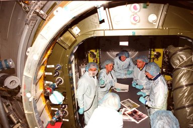 At the Space Station Processing Facility, the Expedition Two crew check out the inside of the air lock. Cosmonaut Yury Usachev is at left; astronaut Susan Helms is seated, center; and astronaut James Voss is second from right. They are joined by astronaut John Young, at right, who flew on mission STS-1. Voss, Helms and Usachev will be flying on mission STS-102, launching March 8, to the International Space Station. The air lock will be carried to the Station during their tenure in space. STS-102 will be Helms? and Voss?s fifth Shuttle flight, and Usachev?s second. They will be replacing the Expedition One crew (Bill Shepherd, Yuri Gidzenko and Sergei Krikalev), who will return to Earth March 20 on Discovery along with the STS-102 crew