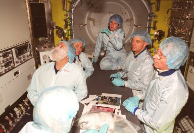 Inside the air lock in the Space Station Processing Facility, the Expedition Two crew look at equipment. Seen from left are cosmonaut Yury Usachev, a technician, and astronauts Susan Helms and James Voss. At far right is astronaut John Young, who flew on mission STS-1. Usachev, Helms and Voss will be flying on mission STS-102, launching March 8. The air lock will be carried to the Station during their tenure in space. STS-102 will be Helms? and Voss?s fifth Shuttle flight, and Usachev?s second. They will be replacing the Expedition One crew (Bill Shepherd, Yuri Gidzenko and Sergei Krikalev), who will return to Earth March 20 on Discovery along with the STS-102 crew