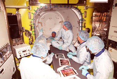 The Expedition Two crew, along with workers at the Space Station Processing Facility, inspect the air lock from the inside. From left are cosmonauts Yury Usachev (foreground, back to camera) and astronauts Susan Helms (seated) James Voss and John Young, who flew on mission STS-1. Voss, Helms and Usachev will be flying on mission STS-102, launching March 8, to the International Space Station. The air lock will be carried to the Station during their tenure in space. STS-102 will be Helms? and Voss?s fifth Shuttle flight, and Usachev?s second. They will be replacing the Expedition One crew (Bill Shepherd, Yuri Gidzenko and Sergei Krikalev), who will return to Earth March 20 on Discovery along with the STS-102 crew
