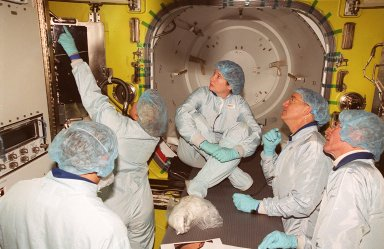 Inside the air lock in the Space Station Processing Facility, a technician points to part of the equipment. Watching her are (left to right) cosmonaut Yury Usachev (back to camera), astronaut Susan Helms (seated), astronauts James Voss and John Young, who flew on mission STS-1. Voss, Helms and Usachev will be flying on mission STS-102, launching March 8, to the International Space Station. The air lock will be carried to the Station during their tenure in space. STS-102 will be Helms? and Voss?s fifth Shuttle flight, and Usachev?s second. They will be replacing the Expedition One crew (Bill Shepherd, Yuri Gidzenko and Sergei Krikalev), who will return to Earth March 20 on Discovery along with the STS-102 crew