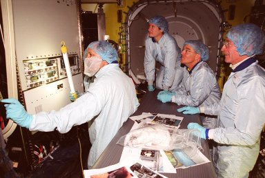Inside the air lock in the Space Station Processing Facility, the Expedition Two crew look at equipment. Seen from left are cosmonaut Yury Usachev and astronauts Susan Helms and James Voss. At far right is astronaut John Young, who flew on mission STS-1. Usachev, Helms and Voss will be flying on mission STS-102, launching March 8. The air lock will be carried to the Station during their tenure in space. STS-102 will be Helms? and Voss?s fifth Shuttle flight, and Usachev?s second. They will be replacing the Expedition One crew (Bill Shepherd, Yuri Gidzenko and Sergei Krikalev), who will return to Earth March 20 on Discovery along with the STS-102 crew