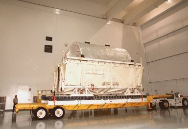 The lid is off the shipping container with the Multi-Purpose Logistics Module Donatello inside. It sits on a transporter inside the Space Station Processing Facility. In the SSPF, Donatello will undergo processing by the payload test team, including integrated electrical tests with other Station elements in the SSPF, leak tests, electrical and software compatibility tests with the Space Shuttle (using the Cargo Integrated Test equipment) and an Interface Verification Test once the module is installed in the Space Shuttle?s payload bay at the launch pad. The most significant mechanical task to be performed on Donatello in the SSPF is the installation and outfitting of the racks for carrying the various experiments and cargo. Donatello will be launched on mission STS-130, currently planned for September 2004