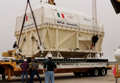 At the Shuttle Landing Facility, workers watch as cranes lower the Italian Space Agency?s Multi-Purpose Logistics Module Donatello onto a flat bed for transport to the Space Station Processing Facility for processing. Among the activities for the payload test team are integrated electrical tests with other Station elements in the SSPF, leak tests, electrical and software compatibility tests with the Space Shuttle (using the Cargo Integrated Test equipment) and an Interface Verification Test once the module is installed in the Space Shuttle?s payload bay at the launch pad. The most significant mechanical task to be performed on Donatello in the SSPF is the installation and outfitting of the racks for carrying the various experiments and cargo