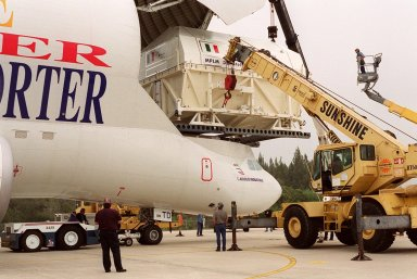 At the Shuttle Landing Facility, workers in cherry pickers (right) help guide offloading of the Italian Space Agency?s Multi-Purpose Logistics Module Donatello from the Airbus ?Beluga? air cargo plane that brought it from the factory of Alenia Aerospazio in Turin, Italy. The third of three for the International Space Station, the module will be transported to the Space Station Processing Facility for processing. Among the activities for the payload test team are integrated electrical tests with other Station elements in the SSPF, leak tests, electrical and software compatibility tests with the Space Shuttle (using the Cargo Integrated Test equipment) and an Interface Verification Test once the module is installed in the Space Shuttle?s payload bay at the launch pad. The most significant mechanical task to be performed on Donatello in the SSPF is the installation and outfitting of the racks for carrying the various experiments and cargo