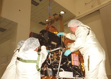 In the Spacecraft Assembly and Encapsulation Facility 2, workers help put the Thermal Emission Imaging System (THEMIS) in its place on the Mars Odyssey Orbiter. THEMIS will map the mineralogy and morphology of the Martian surface using a high-resolution camera and a thermal infrared imaging spectrometer. The orbiter will carry three science instruments: THEMIS, the Gamma Ray Spectrometer (GRS), and the Mars Radiation Environment Experiment (MARIE). The GRS will achieve global mapping of the elemental composition of the surface and determine the abundance of hydrogen in the shallow subsurface. The MARIE will characterize aspects of the near-space radiation environment with regards to the radiation-related risk to human explorers. The Mars Odyssey Orbiter is scheduled for launch on April 7, 2001, aboard a Delta 7925 rocket from Launch Pad 17-A, Cape Canaveral Air Force Station