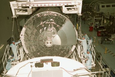 """Workers in the Space Station Processing Facility steady the Multi-Purpose Logistics Module Leonardo as it is lowered toward the weight and balance scale. The Italian-built MPLM is one of three such pressurized modules that will serve as the International Space Station's """"moving vans,"""" carrying laboratory racks filled with equipment, experiments and supplies to and from the station aboard the Space Shuttle. The cylindrical module is approximately 21 feet long and 15 feet in diameter, weighing almost 4.1 metric tons. It can carry up to 9.1 metric tons of cargo packed into 16 standard space station equipment racks. The Leonardo will be launched on mission STS-102 March 8. On that flight, Leonardo will be filled with equipment and supplies to outfit the U.S. laboratory module, to be carried to the ISS on the Feb. 7 launch of STS-98"""