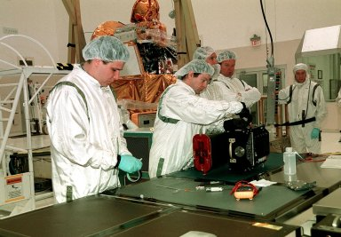 At a work bench in the Spacecraft Assembly and Encapsulation Facility 2, workers test the Thermal Emission Imaging System (THEMIS) before attaching to the 2001 Mars Odyssey Orbiter. THEMIS will map the mineralogy and morphology of the Martian surface using a high-resolution camera and a thermal infrared imaging spectrometer. The orbiter will carry three science instruments: THEMIS, the Gamma Ray Spectrometer (GRS), and the Mars Radiation Environment Experiment (MARIE). The GRS will achieve global mapping of the elemental composition of the surface and determine the abundance of hydrogen in the shallow subsurface. The MARIE will characterize aspects of the near-space radiation environment with regards to the radiation-related risk to human explorers. The Mars Odyssey Orbiter is scheduled for launch on April 7, 2001, aboard a Delta 7925 rocket from Launch Pad 17-A, Cape Canaveral Air Force Station