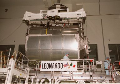 """The Multi-Purpose Logistics Module Leonardo is lifted from its stand in the Space Station Processing Facility to move it to the weight and balance scale. The Italian-built MPLM is one of three such pressurized modules that will serve as the International Space Station's """"moving vans,"""" carrying laboratory racks filled with equipment, experiments and supplies to and from the station aboard the Space Shuttle. The cylindrical module is approximately 21 feet long and 15 feet in diameter, weighing almost 4.1 metric tons. It can carry up to 9.1 metric tons of cargo packed into 16 standard space station equipment racks. The Leonardo will be launched on mission STS-102 March 8. On that flight, Leonardo will be filled with equipment and supplies to outfit the U.S. laboratory module, to be carried to the ISS on the Feb. 7 launch of STS-98"""