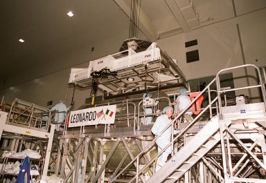 """On a workstand in the Space Station Processing Facility, workers stand by while an overhead crane is ready to lift the Multi-Purpose Logistics Module Leonardo to move it to the weight and balance scale. The Italian-built MPLM is one of three such pressurized modules that will serve as the International Space Station's """"moving vans,"""" carrying laboratory racks filled with equipment, experiments and supplies to and from the station aboard the Space Shuttle. The cylindrical module is approximately 21 feet long and 15 feet in diameter, weighing almost 4.1 metric tons. It can carry up to 9.1 metric tons of cargo packed into 16 standard space station equipment racks. The Leonardo will be launched on mission STS-102 March 8. On that flight, Leonardo will be filled with equipment and supplies to outfit the U.S. laboratory module, to be carried to the ISS on the Feb. 7 launch of STS-98"""