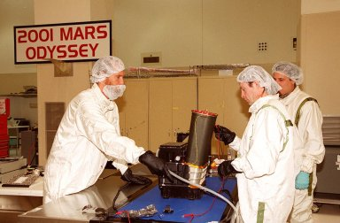 In the Spacecraft Assembly and Encapsulation Facility 2, workers test the Thermal Emission Imaging System (THEMIS) before attaching to the 2001 Mars Odyssey Orbiter. THEMIS will map the mineralogy and morphology of the Martian surface using a high-resolution camera and a thermal infrared imaging spectrometer. The orbiter will carry three science instruments: THEMIS, the Gamma Ray Spectrometer (GRS), and the Mars Radiation Environment Experiment (MARIE). The GRS will achieve global mapping of the elemental composition of the surface and determine the abundance of hydrogen in the shallow subsurface. The MARIE will characterize aspects of the near-space radiation environment with regards to the radiation-related risk to human explorers. The Mars Odyssey Orbiter is scheduled for launch on April 7, 2001, aboard a Delta 7925 rocket from Launch Pad 17-A, Cape Canaveral Air Force Station