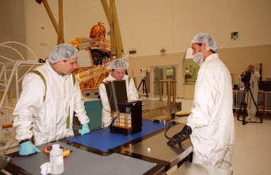 In the Spacecraft Assembly and Encapsulation Facility 2 (SAEF 2), workers check the Thermal Emission Imaging System (THEMIS) before attaching to the 2001 Mars Odyssey Orbiter (background). THEMIS will map the mineralogy and morphology of the Martian surface using a high-resolution camera and a thermal infrared imaging spectrometer. The orbiter will carry three science instruments: THEMIS, the Gamma Ray Spectrometer (GRS), and the Mars Radiation Environment Experiment (MARIE). The GRS will achieve global mapping of the elemental composition of the surface and determine the abundance of hydrogen in the shallow subsurface. The MARIE will characterize aspects of the near-space radiation environment with regards to the radiation-related risk to human explorers. The Mars Odyssey Orbiter is scheduled for launch on April 7, 2001, aboard a Delta 7925 rocket from Launch Pad 17-A, Cape Canaveral Air Force Station