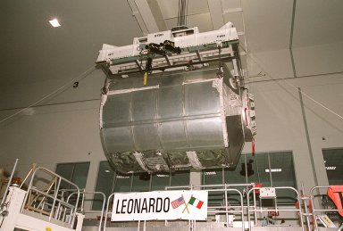 """In the Space Station Processing Facility, an overhead crane begins moving the Multi-Purpose Logistics Module Leonardo to the weight and balance scale. The Italian-built MPLM is one of three such pressurized modules that will serve as the International Space Station's """"moving vans,"""" carrying laboratory racks filled with equipment, experiments and supplies to and from the station aboard the Space Shuttle. The cylindrical module is approximately 21 feet long and 15 feet in diameter, weighing almost 4.1 metric tons. It can carry up to 9.1 metric tons of cargo packed into 16 standard space station equipment racks. The Leonardo will be launched on mission STS-102 March 8. On that flight, Leonardo will be filled with equipment and supplies to outfit the U.S. laboratory module, to be carried to the ISS on the Feb. 7 launch of STS-98"""
