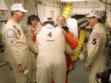 In the White Room before launch, STS-98 Mission Specialist Marsha Ivins gets a hug from a closeout crew member before she enters Space Shuttle Atlantis. The White Room is an environmentally controlled room at the end of the Orbiter Access Arm. Atlantis is carrying the U.S. Laboratory Destiny, a key module in the growth of the Space Station. Destiny will be attached to the Unity node on the Space Station using the Shuttle?s robotic arm. Three spacewalks are required to complete the planned construction work during the 11-day mission. This mission marks the seventh Shuttle flight to the Space Station, the 23rd flight of Atlantis and the 102nd flight overall in NASA?s Space Shuttle program. The planned landing is at KSC Feb. 18 about 1 p.m