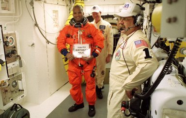 In the White Room with the closeout crew, STS-98 Mission Specialist Robert Curbeam sends a message to his wife before entering Space Shuttle Atlantis for launch. The White Room is an environmentally controlled room at the end of the Orbiter Access Arm. Atlantis is carrying the U.S. Laboratory Destiny, a key module in the growth of the Space Station. Destiny will be attached to the Unity node on the Space Station using the Shuttle?s robotic arm. Three spacewalks are required to complete the planned construction work during the 11-day mission. This mission marks the seventh Shuttle flight to the Space Station, the 23rd flight of Atlantis and the 102nd flight overall in NASA?s Space Shuttle program. The planned landing is at KSC Feb. 18 about 1 p.m