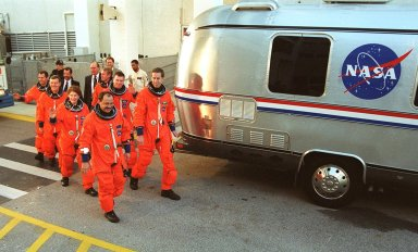 The STS-102 crew heads to the silver Astrovan after leaving the Operations and Checkout Building. In front are Mission Specialist Yury Usachev (left) and Commander James Wetherbee; second are Mission Specialist Susan Helms and Pilot James Kelly; third, Mission Specialists James Voss and Andrew Thomas; and last, Mission Specialist Paul Richards. Voss, Helms and Usachev are the Expedition Two crew, going to the International Space Station for their four-month rotation. The Astrovan will take the crew to Launch Pad 39B for a simulated countdown, part of Terminal Countdown Demonstration Test activities. STS-102 is the eighth construction flight to the Space Station, with Space Shuttle Discovery carrying the Multi-Purpose Logistics Module Leonardo. In addition, Expedition One will return to Earth with Discovery. Launch on mission STS-102 is scheduled for March 8
