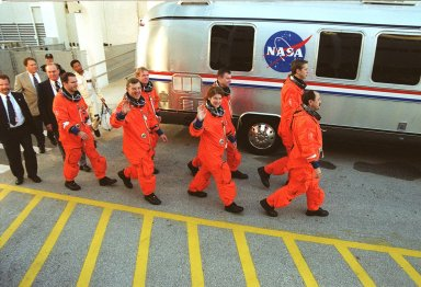 Waving to media and bystanders, the STS-102 crew strides to the silver Astrovan after leaving the Operations and Checkout Building. In front, left to right, are Mission Specialists Paul Richards, James Voss, Susan Helms and Yury Usachev. Behind then are Mission Specialist Andrew Thomas, Pilot James Kelly and Commander James Wetherbee. Voss, Helms and Usachev are the Expedition Two crew, going to the International Space Station for their four-month rotation. The Astrovan will take the crew to Launch Pad 39B for a simulated countdown, part of Terminal Countdown Demonstration Test activities. STS-102 is the eighth construction flight to the Space Station, with Space Shuttle Discovery carrying the Multi-Purpose Logistics Module Leonardo. In addition, Expedition One will return to Earth with Discovery. Launch on mission STS-102 is scheduled for March 8