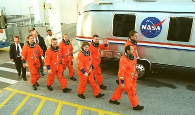 The STS-102 crew heads to the silver Astrovan after leaving the Operations and Checkout Building. In front, left to right, are Mission Specialists Paul Richards, James Voss, Susan Helms and Yury Usachev. Behind then are Mission Specialist Andrew Thomas, Pilot James Kelly and Commander James Wetherbee. Voss, Helms and Usachev are the Expedition Two crew, going to the International Space Station for their four-month rotation. The Astrovan will take the crew to Launch Pad 39B for a simulated countdown, part of Terminal Countdown Demonstration Test activities. STS-102 is the eighth construction flight to the Space Station, with Space Shuttle Discovery carrying the Multi-Purpose Logistics Module Leonardo. In addition, Expedition One will return to Earth with Discovery. Launch on mission STS-102 is scheduled for March 8